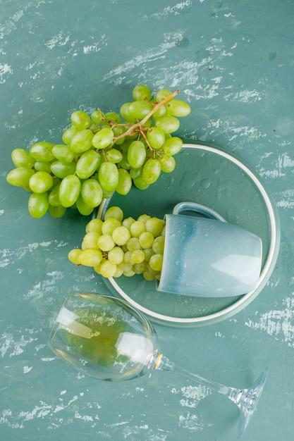 石膏とトレイの背景にドリンクトップビューとカップのブドウ 無料写真