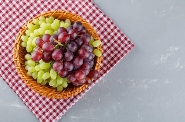 Виноград в плетеной корзине на скатерти и гипсе, Бесплатные Фотографии