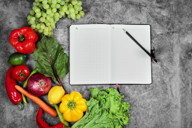 Grapes, peppers, greens, lemon, tomato and empty notebook on marble background. Free Photo
