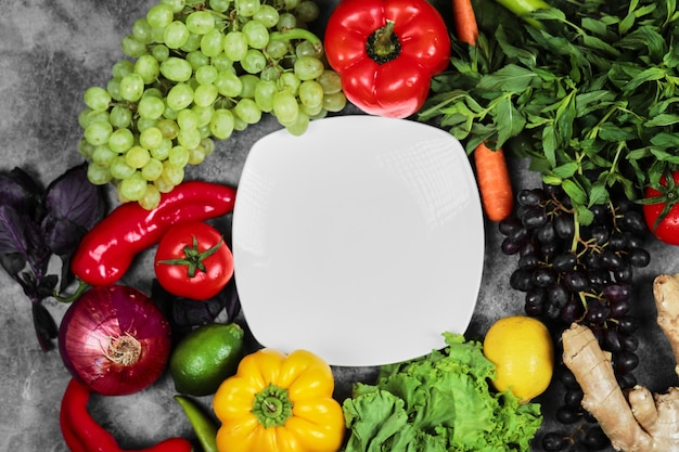 Grapes, peppers, greens, lemon, tomato , ginger and white plate on marble background. Free Photo