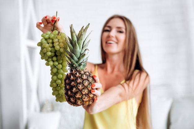 Grapes and pineapple in the hands of a girl Premium Photo