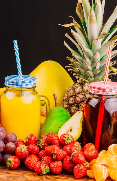 Grapes; strawberries; pears; pineapple and juice bottle against black background Free Photo