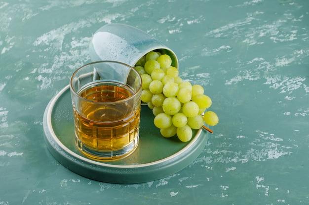 石膏とトレイの背景、高角度のビューの上にカップでドリンクを飲みながらブドウ。 無料写真