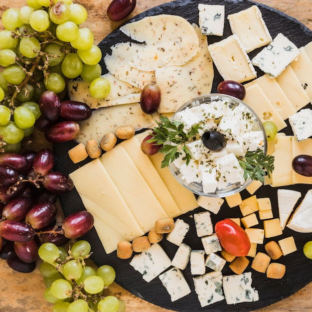Grapes with variety of cheese cubes and slices on black slate board Free Photo