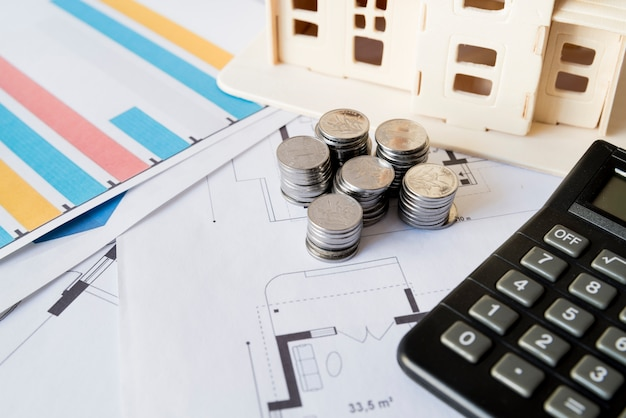 Graph; stack of coins; calculator and house model on blueprint Free Photo