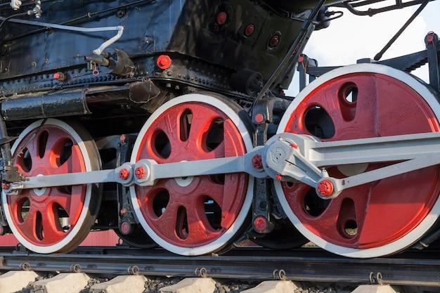 그래프는 빨간색으로 칠해진 검은 색으로 오래 된 증기 기관차 바퀴를 닫습니다. 빨간색으로 표시되었습니다. 프리미엄 사진