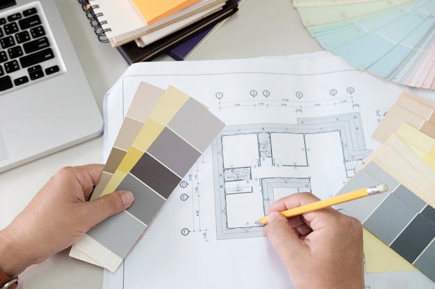책상에 그래픽 디자인 및 색상 견본 및 펜. 작업 도구 및 액세서리로 건축 도면. 무료 사진
