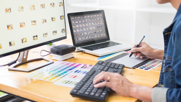 Graphic designer team working on web design using color swatches editing artwork using tablet and a stylus at desks in busy creative office. Premium Photo