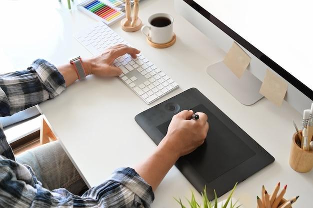 Graphic designer using digital tablet with desktop computer in studio office Premium Photo