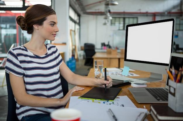 Graphic designer using  graphic tablet and desktop Premium Photo