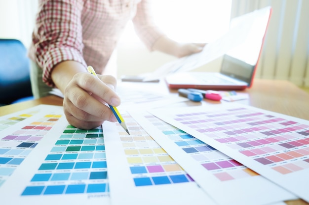 Graphic designer at work. color swatch samples. Free Photo