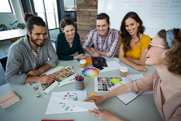 Графические дизайнеры обсуждают друг с другом на встрече Premium Фотографии