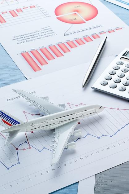 Graphs and histograms, calculator andairplane. Premium Photo