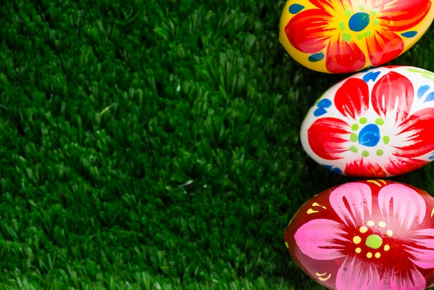 Grass surface with three colorful easter eggs Free Photo