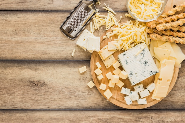 Grated cheese, cheese blocks and bread sticks over the desk Free Photo