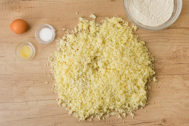 Grated cheese; salt; egg; flour for preparing italian gnocchi on wooden desk Free Photo
