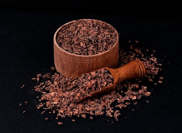 Grated chocolate on black background, closeup Premium Photo