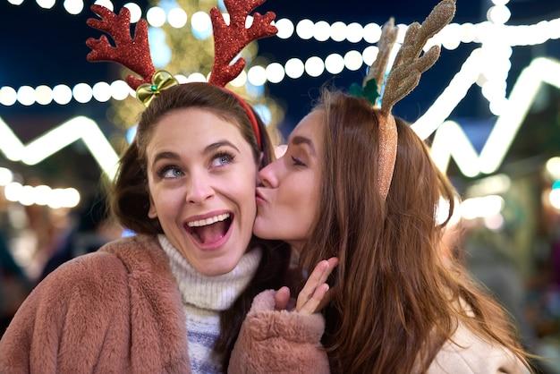 クリスマスマーケットでキスをする感謝の女性 無料写真