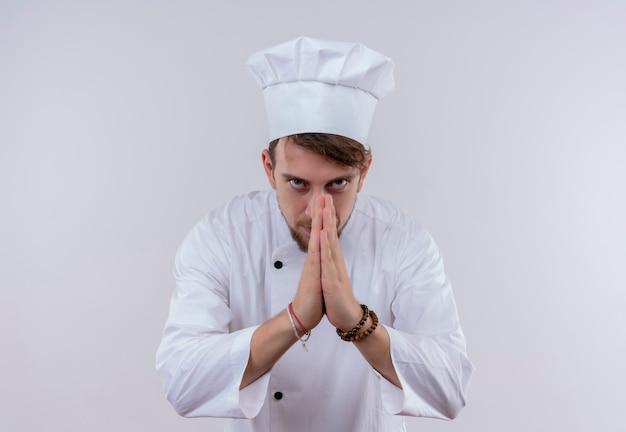 Un giovane uomo barbuto grato del cuoco unico in uniforme bianca che si tiene per mano nel gesto di apprezzamento mentre osserva su una parete bianca Foto Gratuite