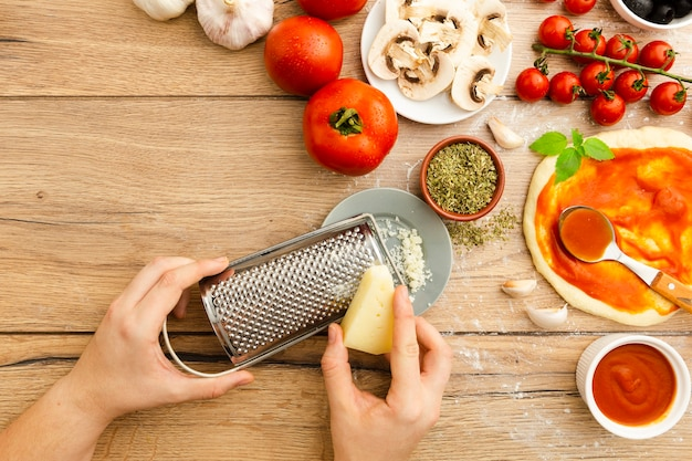 Grating cheese with other pizza ingredients Free Photo