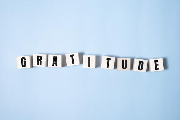 Слово благодарности, написанное на деревянном блоке. текст благодарности на синем столе для вашего дизайна, концепции. Premium Фотографии