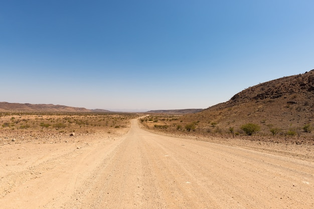 Gravel 4x4 road crossing the colorful desert at twyfelfontein, in the majestic damaraland brandberg, scenic travel destination in namibia, africa. Premium Photo