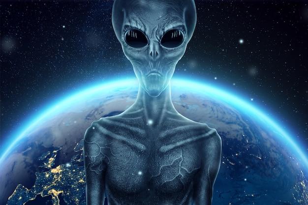 Серый инопланетянин, гуманоид, с черными большими стеклянными глазами на фоне земного шара. концепция нло, инопланетяне, контакт с внеземной цивилизацией. Premium Фотографии