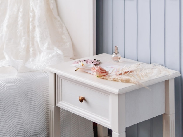 Gray bedside table with bridal accessories. decorative monstera leaves and pampas grass, pale pink rose flowers and a bottle of perfume. Premium Photo