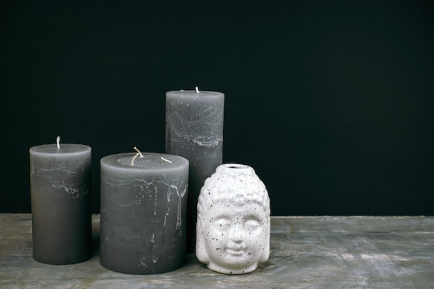 Gray candles and white ceramic buddha head on a table opposite black wall Premium Photo