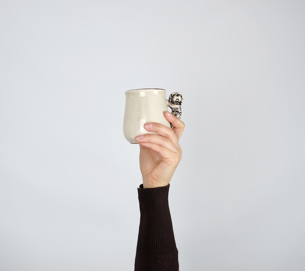 Gray ceramic cup in female hand on a white background, hand raised up Premium Photo