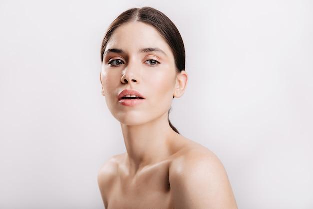 Modello femminile dagli occhi grigi con capelli scuri con pelle sana che posa sensualmente sul muro bianco. Foto Gratuite