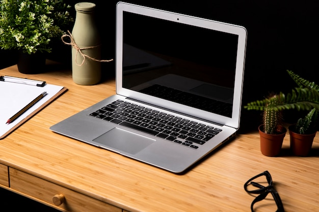 Gray laptop on simple wooden desk Free Photo