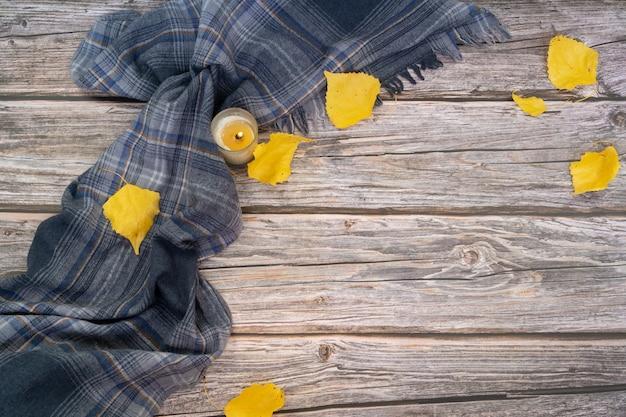 Серый шарф и сухие листья желтого цвета на деревянной поверхности Premium Фотографии