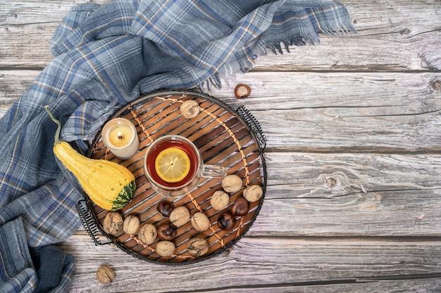 Серый шарф, чай и осенний декор на деревянной поверхности Premium Фотографии