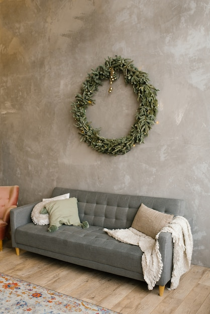 Gray sofa with pillows, over the sofa on the wall hangs a christmas wreath. scandinavian style in the living room Premium Photo