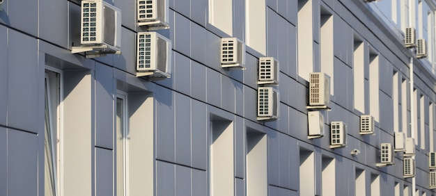 Gray wall of office building made of metal plates with windows and air conditioners Premium Photo