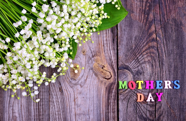 Gray wooden background with the inscription mother's day Premium Photo