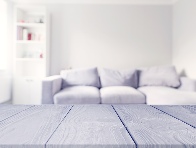 Gray wooden table in front of blur white sofa in the living room Free Photo