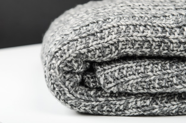Gray wool knitted plaid, lies rolled up on white table. close up. Premium Photo