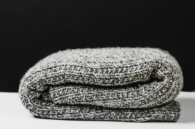 Gray wool knitted plaid, lies rolled up on white table. Premium Photo
