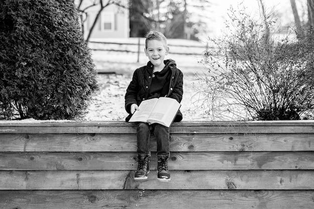 Scala di grigi di un ragazzo felice seduto su una staccionata in legno e leggendo un libro in un parco Foto Gratuite