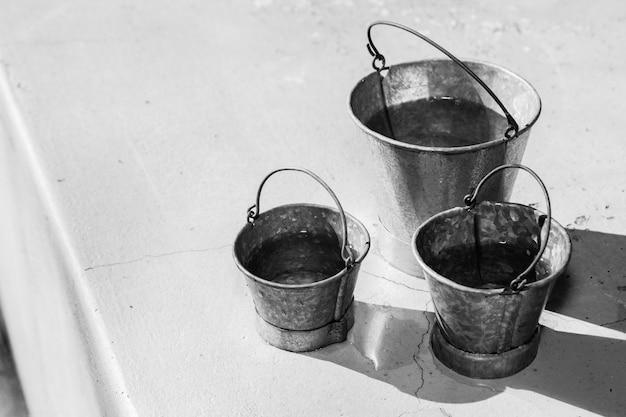 Colpo in scala di grigi di diverse dimensioni di secchi metallici Foto Gratuite