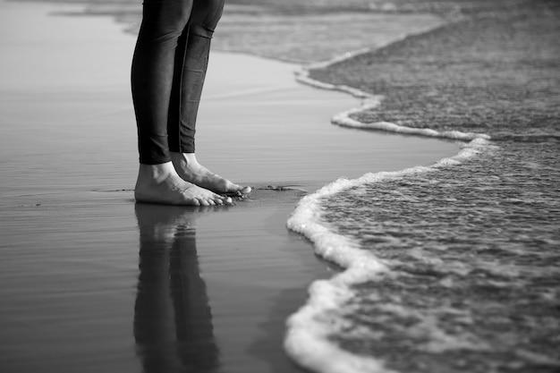 Colpo in scala di grigi delle gambe a piedi nudi dell'essere umano in piedi su una spiaggia sabbiosa Foto Gratuite