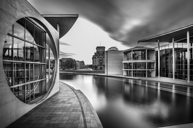 Grayscale shot of a lake in the middle of city buildings under a cloudy sky Free Photo
