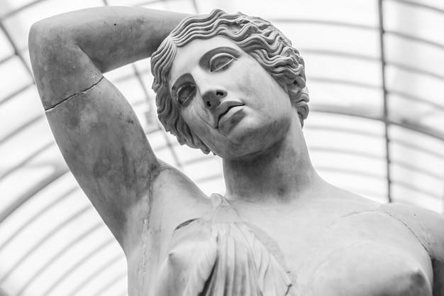 Scatto in scala di grigi di una statua in marmo di una donna sotto le luci Foto Gratuite