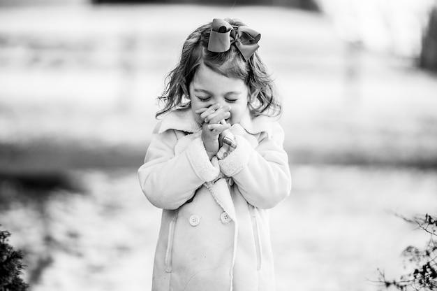 Снимок в оттенках серого: милая девушка загадывает желание с закрытыми глазами Бесплатные Фотографии