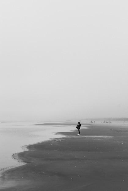 Снимок в оттенках серого: одинокий человек идет по пляжу в темных облаках Бесплатные Фотографии
