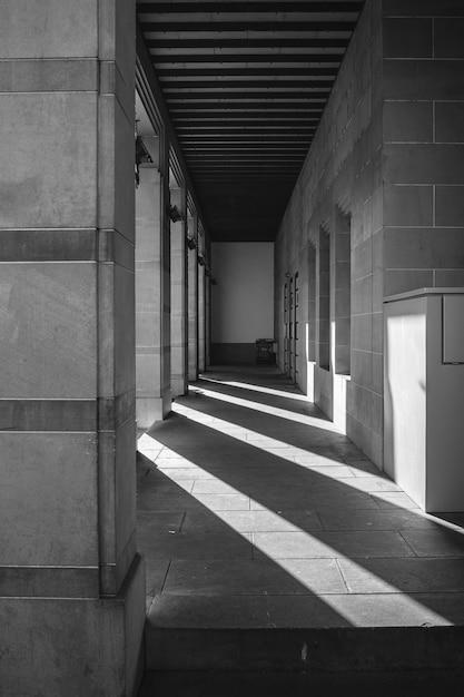 梁の影のある外側の廊下のグレースケールショット 無料写真
