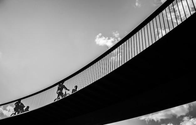 Снимок в оттенках серого: люди, едущие на велосипедах по мосту Бесплатные Фотографии