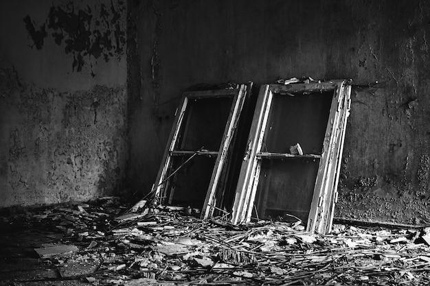 오래된 집의 지저분한 바닥에 놓인 창틀의 그레이 스케일 샷 무료 사진